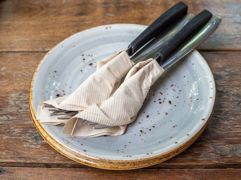 Dwa set czysty rozwidlenie i nóż zawijający w tkankowej pielusze w ceramicznym naczyniu fotografia royalty free