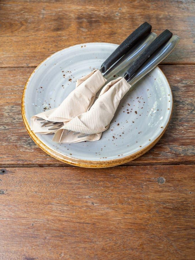 Dwa set czysty rozwidlenie i nóż zawijający w tkankowej pielusze w ceramicznym naczyniu zdjęcia stock