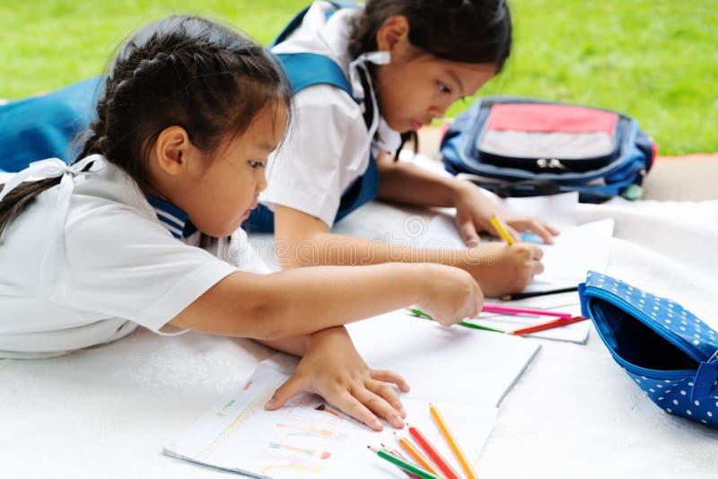 Dwa siostr dziewczyna pisze książki Decyzja lekcje dziewczyna kłaść puszek rysuje obrazek zdjęcia royalty free