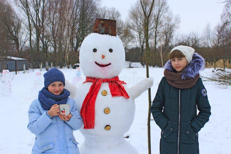 Dwa siostr sztuka blisko bałwanu w zima dniu obraz royalty free