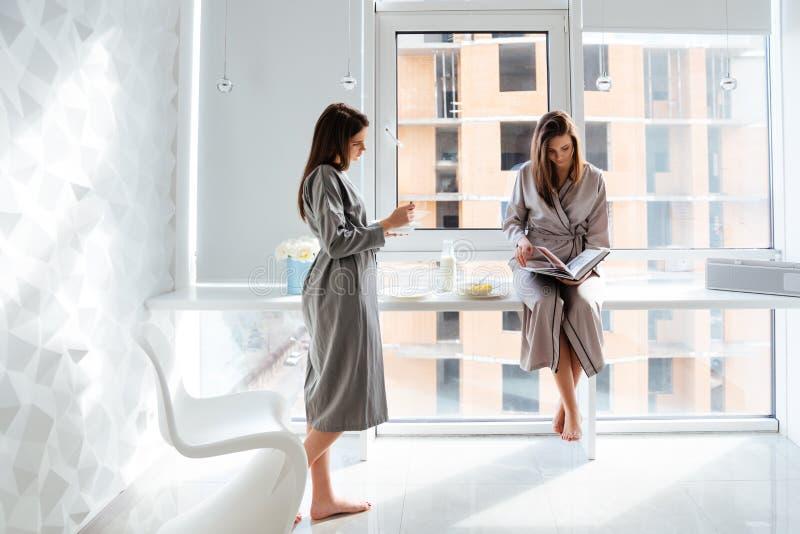 Dwa siostra bliźniaków czytelnicza książka i mieć śniadanie w domu zdjęcie stock