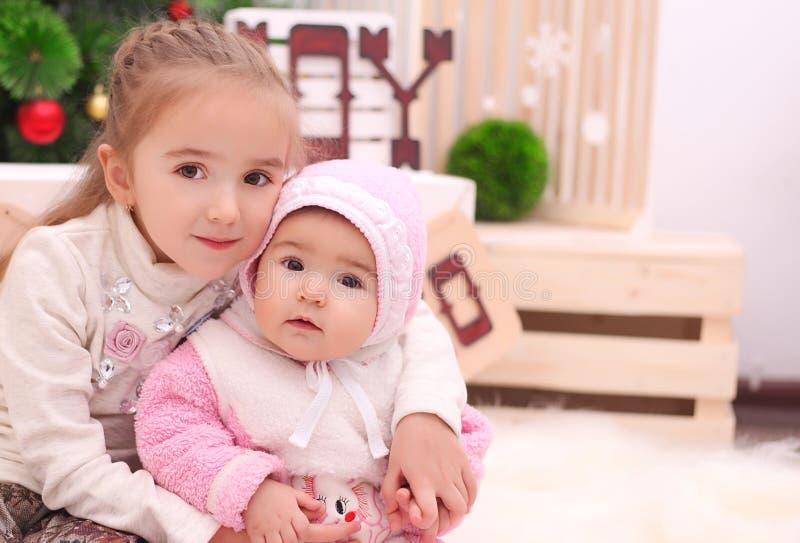 Dwa siostry bawić się z Bożenarodzeniowymi dekoracjami i teraźniejszość siedzi na podłoga piłek bożych narodzeń odosobniony nastr fotografia royalty free