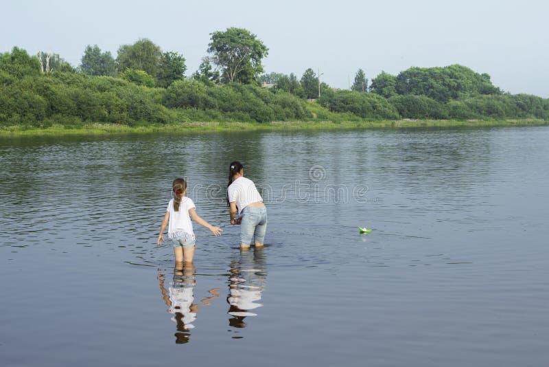 Dwa siostry bawić się z papierowymi łodziami rzeką zdjęcia stock