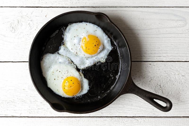 Dwa smażącego jajka w obsady żelaznej smaży niecce kropiącej z zmielonym bla zdjęcie stock