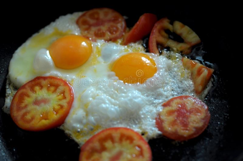 Dwa smażyli jajka w czarnej smaży niecce i pokrajać pomidoru Proces kucharstwo fotografia stock