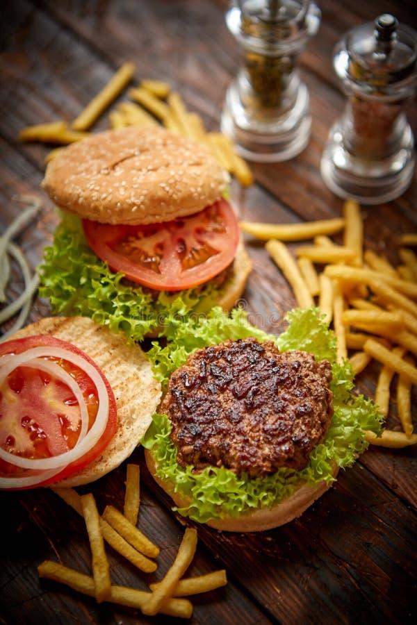 Dwa smakowitego piec na grillu domowego robić hamburgeru z wołowiną, pomidorem, cebulą i sałatą, zdjęcie stock