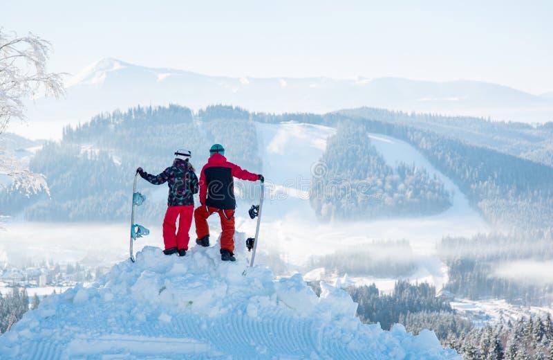 Dwa snowboarders cieszą się śnieżnobiałą scenerię góry i lasy zdjęcia royalty free