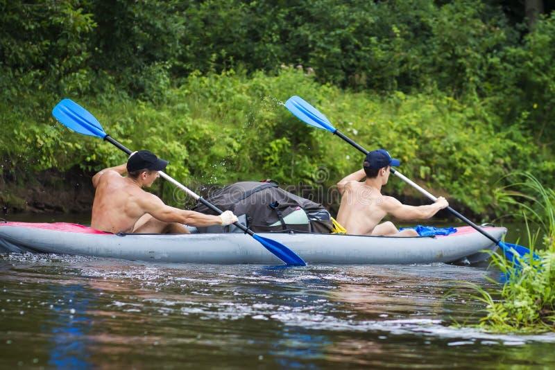 Dwa sportów młody facet w łodzi wioślarskich wiosłach na wodzie Kayaking wzdłuż rzeki w lato sezonie obraz stock