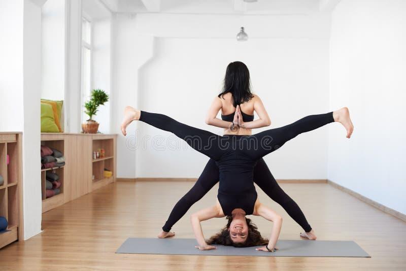 Dwa sporty ludzie praktyki joga w parze Jogowie ?wicz? spe?niania Namaste Tyln? poz? i Headstand z szerokim k?tem i?? na piechot? zdjęcie royalty free