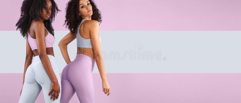 Dwa sprawności fizycznej kobiety w sportswear odizolowywającym nad szarym tłem Sporta i mody pojęcia dowcipu chopy przestrzeń fotografia stock