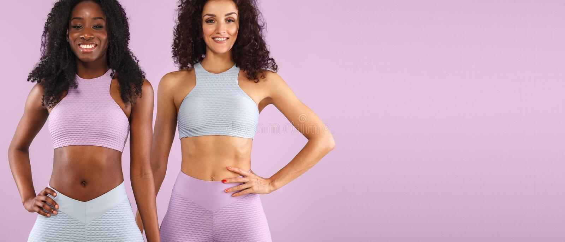 Dwa sprawności fizycznej kobiety w sportswear odizolowywającym nad szarym tłem Sporta i mody pojęcia dowcipu chopy przestrzeń obraz stock