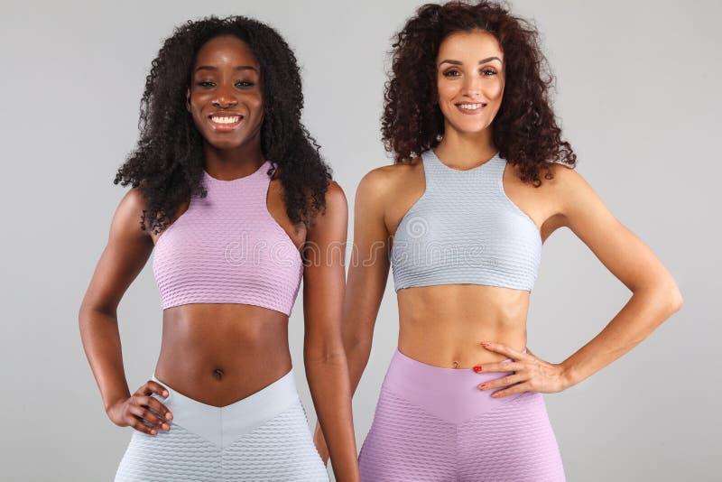 Dwa sprawności fizycznej kobiety w sportswear odizolowywającym nad szarym tłem Sporta i mody pojęcie z kopii przestrzenią zdjęcia royalty free