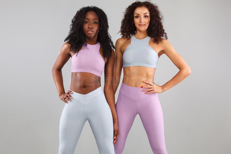 Dwa sprawności fizycznej kobiety w sportswear odizolowywającym nad szarym tłem Sporta i mody pojęcie z kopii przestrzenią obraz royalty free