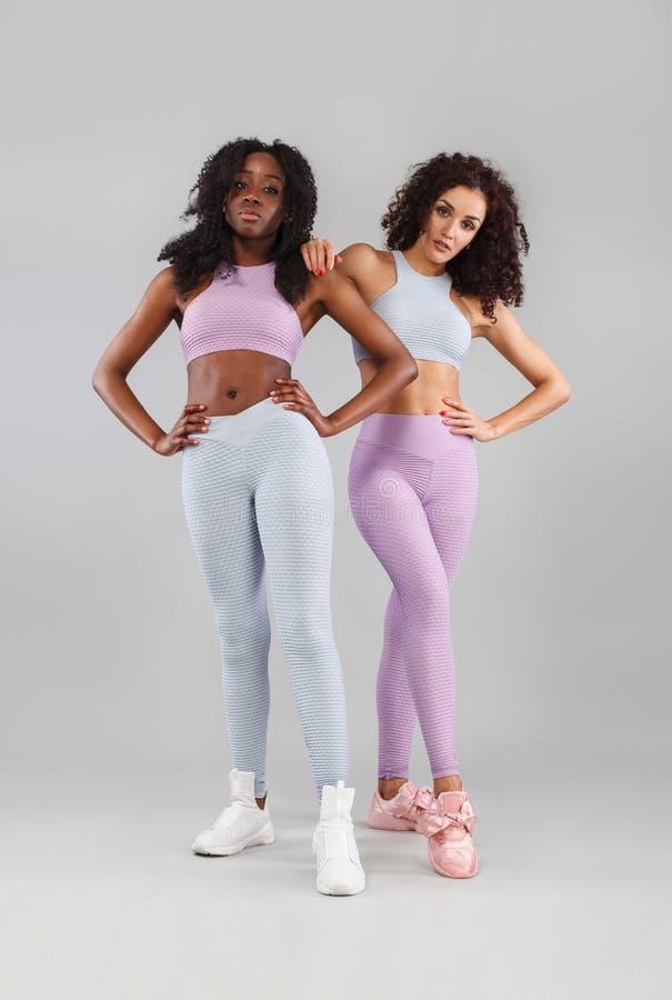 Dwa sprawności fizycznej kobiety w sportswear odizolowywającym nad szarym tłem Sporta i mody pojęcie z kopii przestrzenią obrazy royalty free