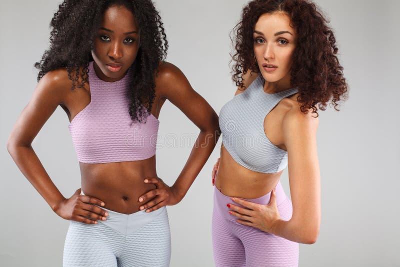 Dwa sprawności fizycznej kobiety w sportswear odizolowywającym nad szarym tłem Sporta i mody pojęcie z kopii przestrzenią zdjęcia stock
