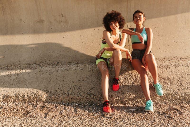 Dwa sprawności fizycznej szczęśliwa dziewczyna relaksuje na molu po trenować fotografia royalty free
