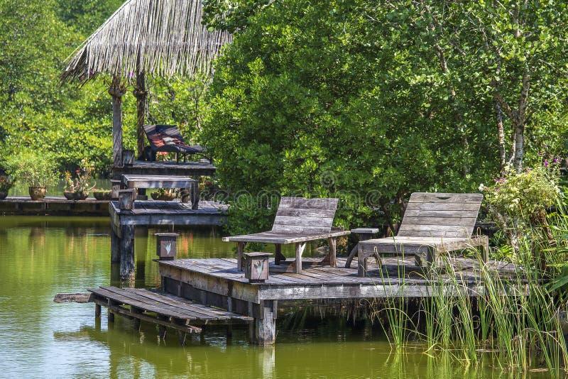 Dwa starego drewnianego pokładu krzesła blisko jezioro wody w tropikalnym ogródzie, Asia, Tajlandia obraz stock