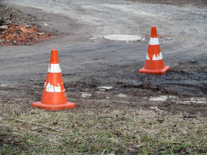 Dwa starego podławego budowa rożka są na drodze gruntowej Pomarańczowy ruch drogowy konusuje z podławymi białymi lampasami przeci obraz royalty free