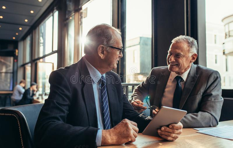Dwa starszego biznesmena ma nieformalnego spotkania przy kawiarnią obraz stock