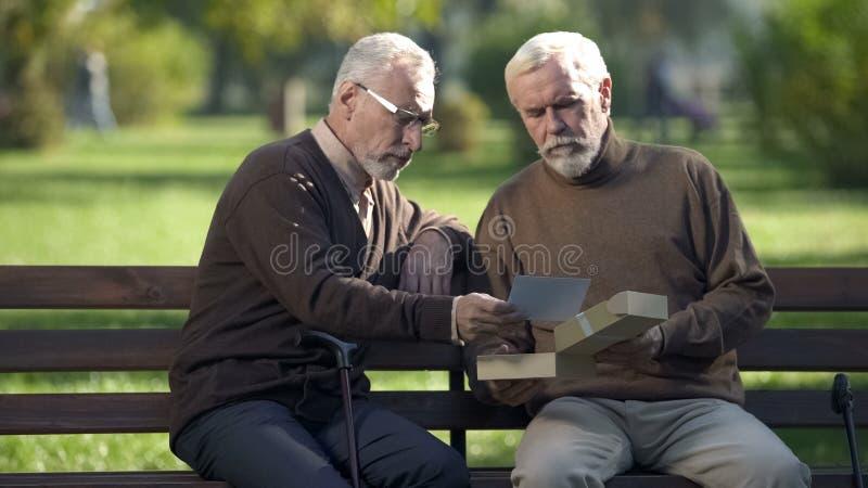 Dwa starszego brata patrzeje fotografi? i pami?ta krewnych, wspominki zdjęcie stock