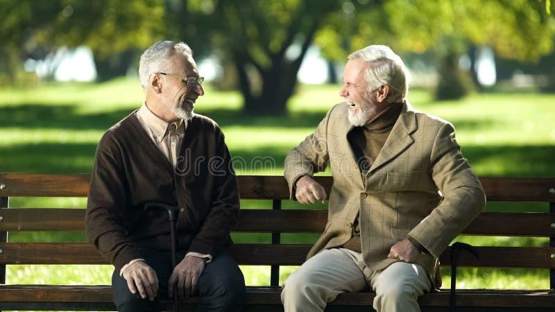 Dwa starszego ludzie śmia się pamiętający młodych rok siedzi na ławce w parku obraz royalty free