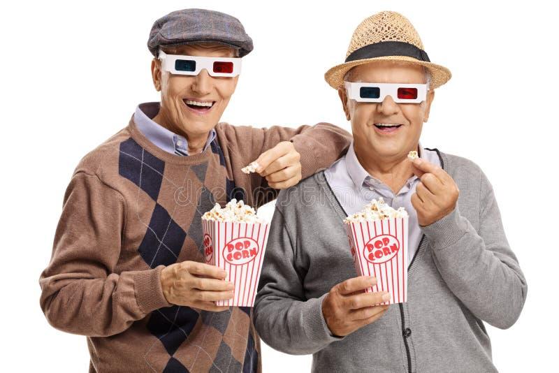 Dwa starszego mężczyzna jest ubranym 3D szkła i ma popkorn obrazy royalty free
