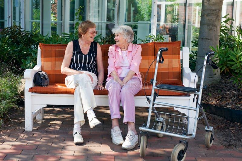 Dwa starszego przyjaciela gawędzi na parkowej ławce zdjęcia royalty free