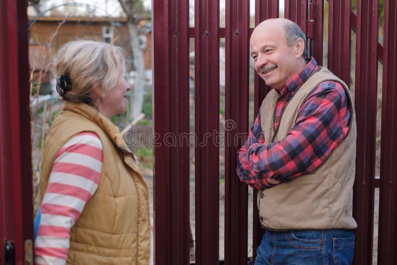 Dwa starszego s?siad takling na s?onecznym dniu blisko do siebie one fechtuj? si? obraz stock