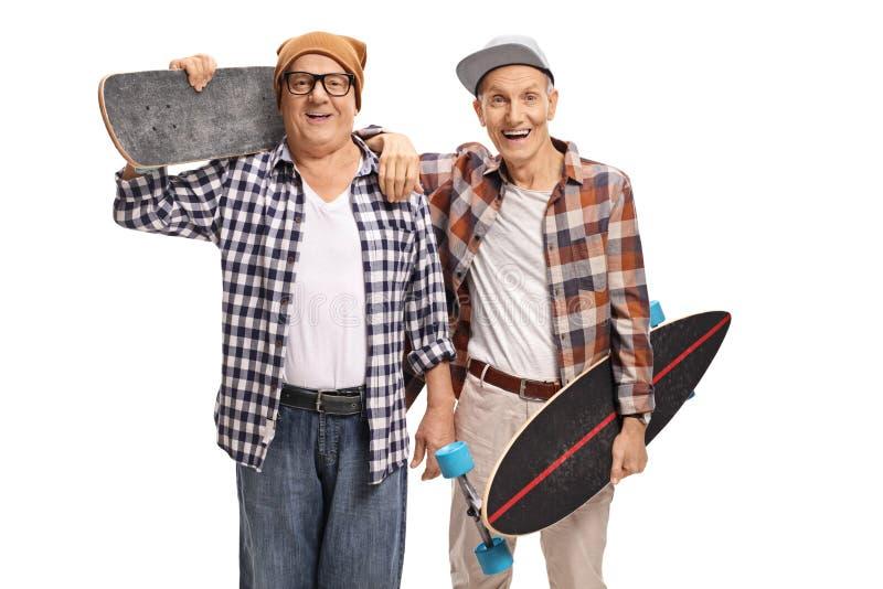 Dwa starszej łyżwiarki patrzeje sm i kamerę z longboards obrazy royalty free
