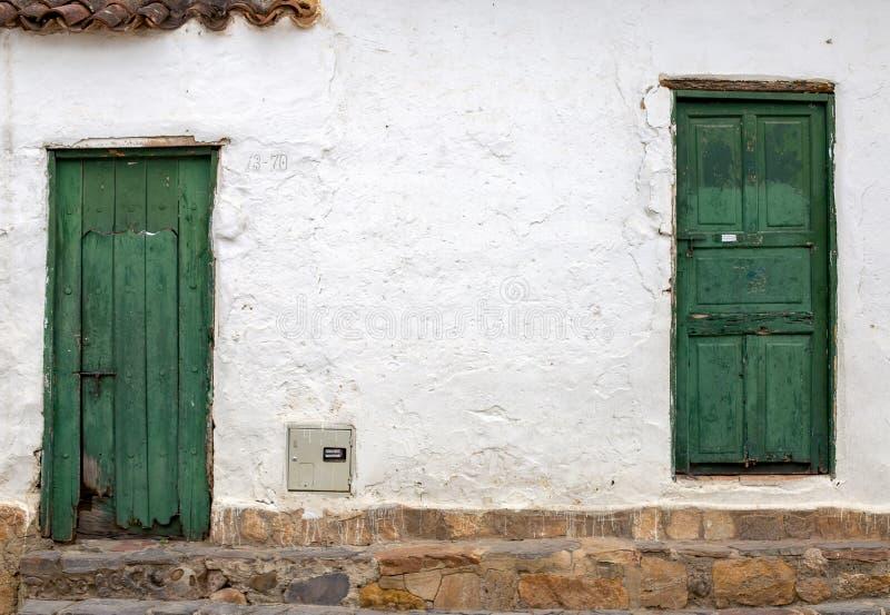 Dwa stary i uszkadzający zieleni drzwi zdjęcie royalty free