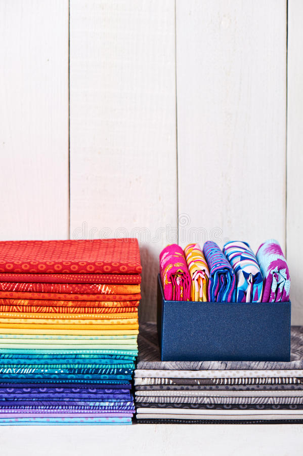 Dwa stos kawałka stebnowania kolorowe tkaniny na białym drewnianym tle fotografia stock