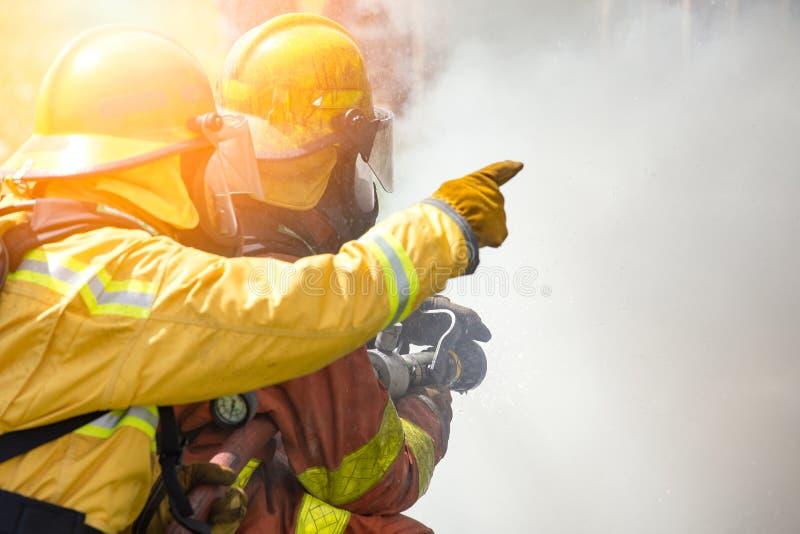 Dwa strażaków wodna kiść wysokość naciska nozzle podpalać sura zdjęcie royalty free