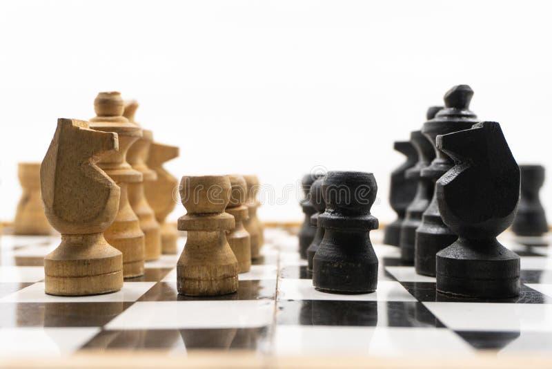 Dwa strony czarny i biały szachowi kawałki stawiają czoło each inny, które zrobią drewno, Tam jest biały tło dla umieszczać obraz stock