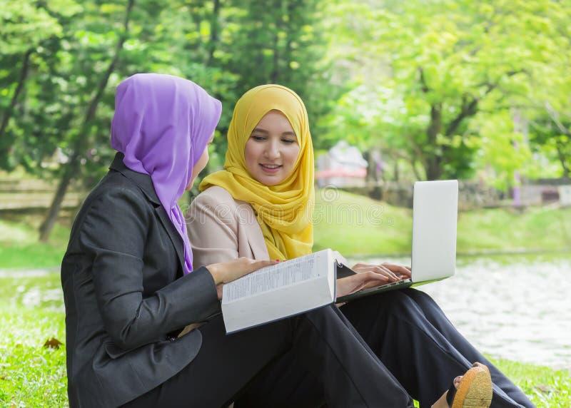 Dwa studenta collegu ma dyskusję i zmienia pomysły w parku podczas gdy siedzący obrazy stock