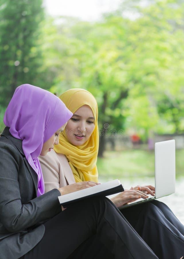 Dwa studenta collegu ma dyskusję i zmienia pomysły w parku podczas gdy siedzący zdjęcia stock