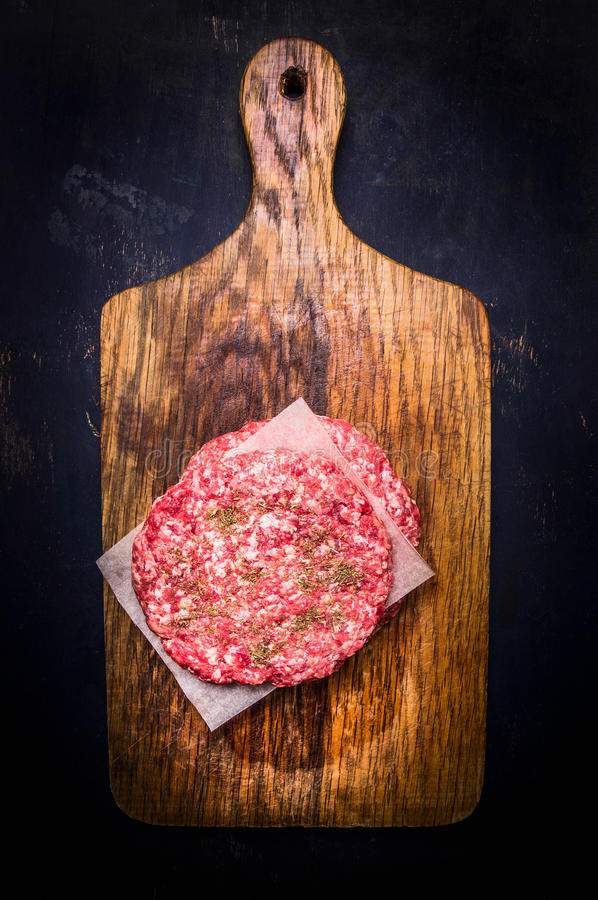 Dwa surowy cutlet dla hamburgeru na tnącej desce z koperkowym drewnianym nieociosanym tło odgórnego widoku zakończeniem up zdjęcia stock
