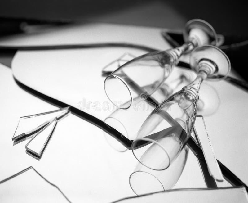 Dwa szampańskiego szkła na łamanych lustrzanych kawałkach Czarny i biały tło - pecha małżeństwa pojęcia tło z kopii przestrzenią  zdjęcie stock
