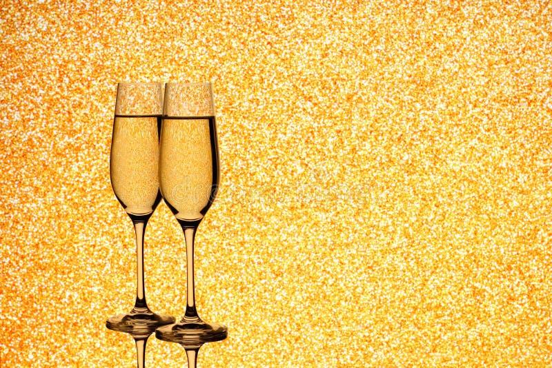 Dwa szampańskiego szkła na zamazanym złotym tle fotografia royalty free