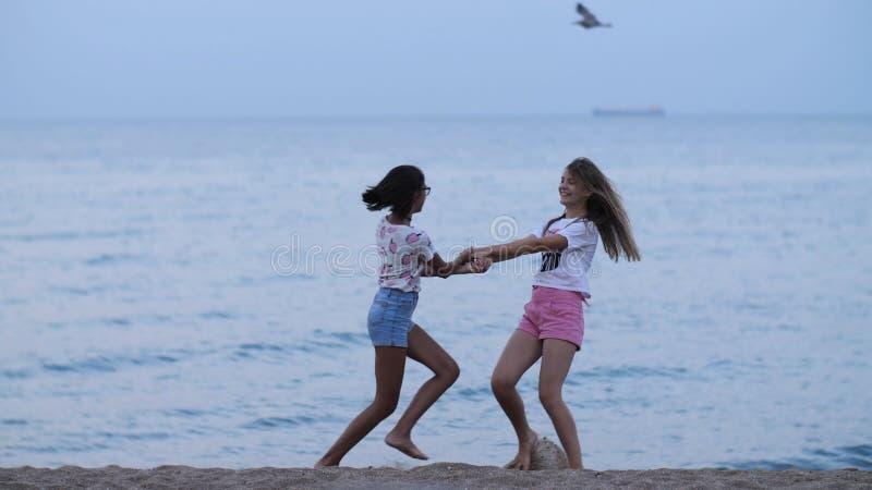 Dwa szczęśliwej dziewczyny kłębi przy plażą blisko morza w wieczór obraz royalty free