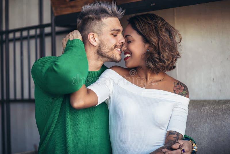 Dwa szczęśliwa mieszana biegowa para ma zabawę przy sklep z kawą zdjęcie royalty free