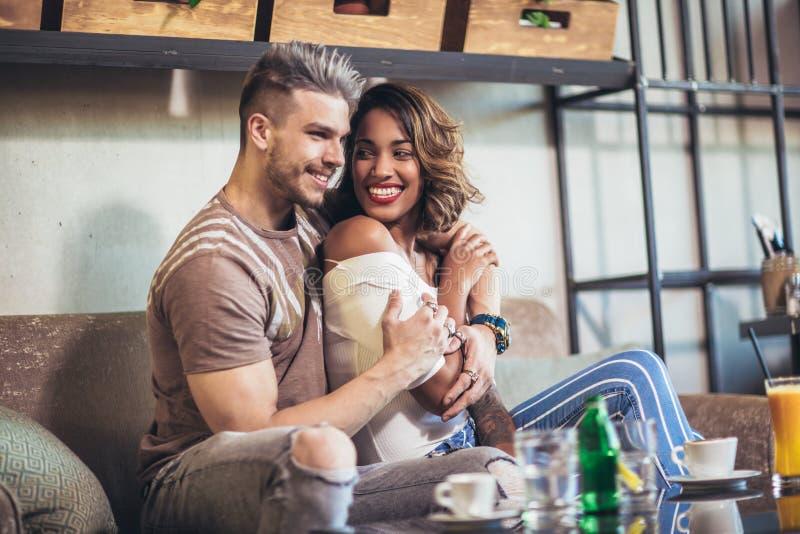 Dwa szczęśliwa mieszana biegowa para ma zabawę przy sklep z kawą obraz royalty free