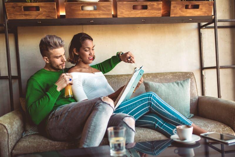 Dwa szczęśliwa mieszana biegowa para ma zabawę przy sklep z kawą obrazy royalty free