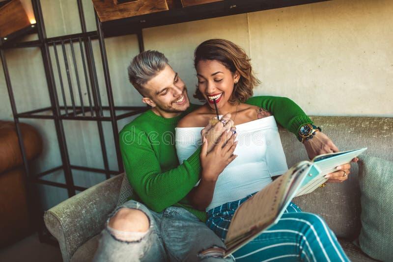 Dwa szczęśliwa mieszana biegowa para ma zabawę przy sklep z kawą zdjęcia stock