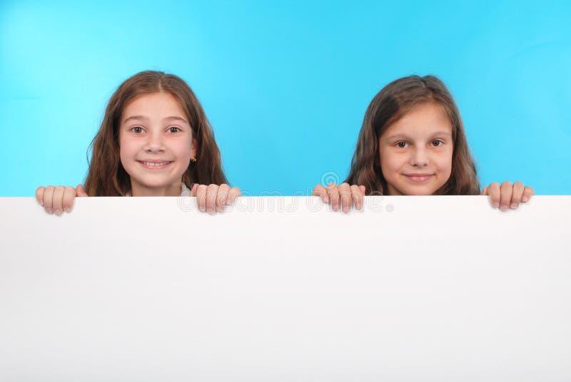 Dwa szczęśliwa uśmiechnięta piękna młoda dziewczyna pokazuje pustego signboard lub copyspace dla sloganu lub teksta zdjęcie stock