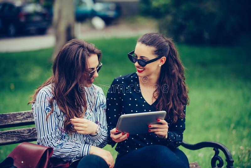 Dwa szczęśliwego żeńskiego przyjaciela śmia się dopatrywanie środki zadawalają wpólnie w cyfrowej pastylce zdjęcie stock