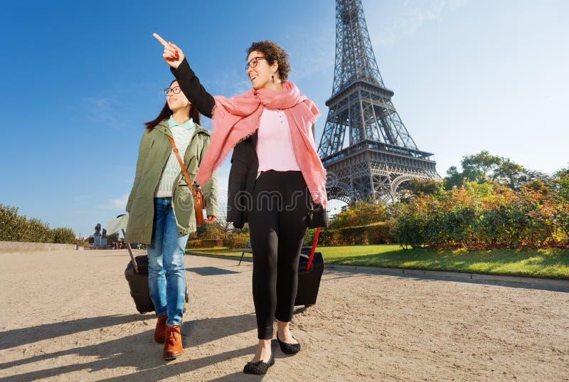 Dwa szczęśliwego żeńskiego turysty chodzi wokoło Paryż obraz stock