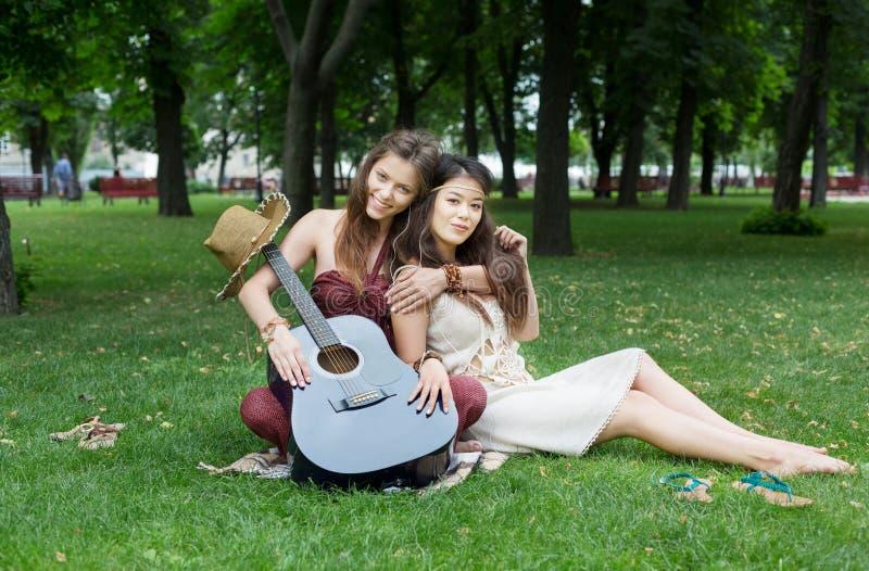 Dwa szczęśliwego boho modnej eleganckiej dziewczyny pyknicznej w parku zdjęcie stock