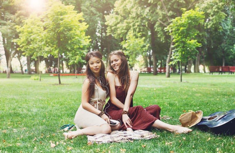 Dwa szczęśliwego boho modnej eleganckiej dziewczyny pyknicznej w parku fotografia stock