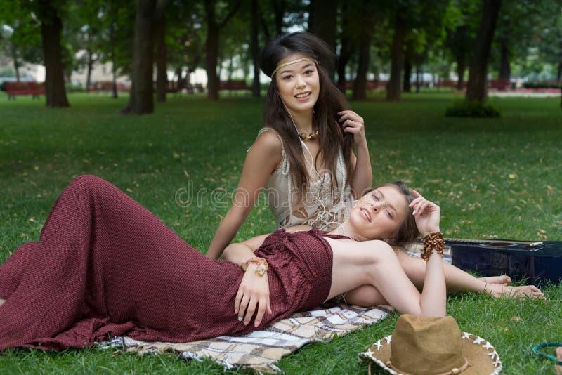 Dwa szczęśliwego boho modnej eleganckiej dziewczyny z gitarą, pinkin obraz royalty free