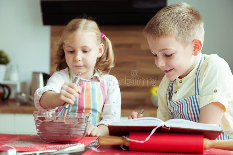 Dwa szczęśliwego dziecka piec bożych narodzeń ciastka przy kuchnią obraz royalty free